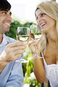 young couple enjoying a glass of white wine in the garden on a summer day