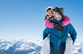 Young couple having fun on snow. Happy man at the mountain giving piggyback ride to his smiling girl poster