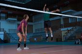 Full length of woman looking at male teammate jumping at volleyball court poster