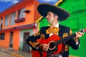 Charro Mariachi singer playing guitar in Mexico houses background