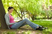foto of teenage girl  - young girl sitting next tree and reading book in nature - JPG