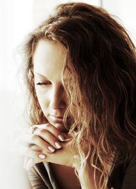 stock photo of sad face  - Sad woman against a window - JPG