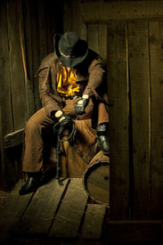 foto of flogging  - Cowboy with Black Leather Flogging Whip in his hand against wooden background - JPG