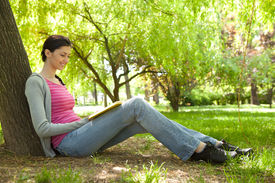 image of teenage girl  - young girl sitting next tree and reading book in nature - JPG