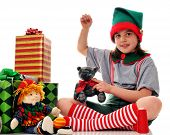 stock photo of knee-high socks  - An elf sewing a stuffed animal for Santa to give away on Christmas Eve - JPG