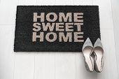 Modern condo businesswoman high heel shoes at home on entrance doormat saying Home Sweet Home welcom poster