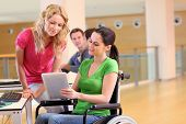 stock photo of young girls  - Handicapped person at work with electronic tablet - JPG
