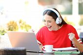 Excited Student E-learning With A Laptop And Headphones Finds Offers In A Coffee Shop Terrace poster