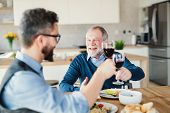 An Adult Hipster Son And Senior Father Indoors At Home, Eating Light Lunch. poster