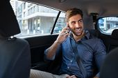 Young smiling man talking over phone while sitting in taxi. Happy business man sitting on back seat  poster