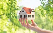 real estate, accommodation and eco friendly concept - close up of hand holding house or home model o poster