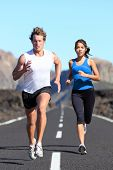 Running couple. Runners outdoor jogging workout on road beautiful landscape. Fit athletes training,