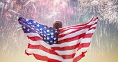 Patriotic holiday. Happy young woman with American flag looking at fireworks. USA celebrate 4th of J poster