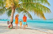 Family on beach, young couple in orange with three year old boy under the palm tree. Summer vacation poster