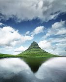 Gorgeous landscape with Kirkjufell mountain, clear lake and cloudscape in blue sky poster
