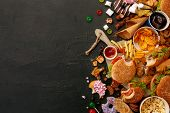 Fast Food Dish On Black Stone Background. Take Away Unhealthy Set Including Burgers, Sauces, French  poster