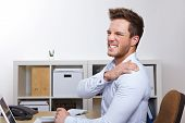 Business man with shoulder pain in office at desk