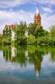 Landshut townscape with Christ Church (Christuskirche) reflecting in Isar river on a bright spring d poster