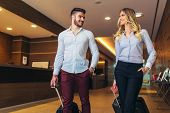 Young Couple Near Reception Desk In Hotel. Young Couple Leaving Hotel poster