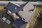 Aerial Top View Of Building Steep Shingle Roof, Brick Chimneys And Small Attic Window On House Top W poster