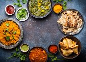 Overhead Of Indian Traditional Dishes And Appetizers: Chicken Curry, Pilaf, Naan Bread, Samosas, Pan poster