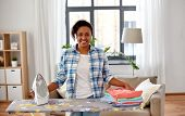 housework, laundry and housekeeping concept - happy african american woman with ironed clothes on ir poster