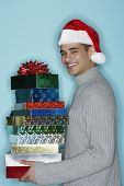 Young man holding holiday gifts