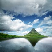 Landscape with Kirkjufell mountain, clear lake and cloudscape in blue sky poster
