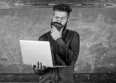Distance Education Concept. Surfing Internet. Hipster Teacher Wear Eyeglasses And Necktie Holds Lapt poster