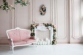 Elegant White Fireplace Full Of Flowers. Elegant White Room With A Sofa. Wedding Area. Vintage Decor poster