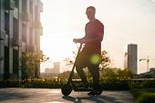 Man Riding Black Electric Kick Scooter At Cityscape Background At Sunset poster
