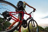 pic of bicycle gear  - Young woman with backpack and bicycle walking on countryside terrain - JPG
