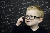 stock photo of cheeky  - Smart young boy wearing a navy blue jumper and glasses stood infront of a blackboard with scientific formulas and equations written in chalk - JPG