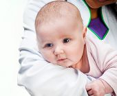 Small baby in doctors hands isolated on a white background
