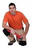 Kneeling handyman holding a pipe wrench