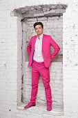 Young man in pink suit and shoes stands with his hands on hips in wall aperture