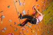 The girl climbs the steep wall on the climbing gym