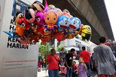KUALA LUMPUR - AUGUST 31: A street vendor sells balloons to revelers on the city streets as they cel