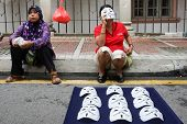 KUALA LUMPUR - AUGUST 31: Street vendors sell celebration masks to revelers on the streets as they c