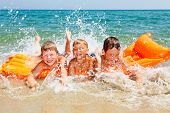 Three kids splashing water on a beach