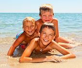 Three kids enjoying summer day on a beach