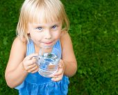 Little girl holding glass of water outdoors