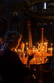 POCHAYIV, UKRAINE - AUGUST 14: Unidentified orthodox believer lights candles in Holy Dormition Pocha
