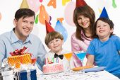 stock photo of party people  - Portrait of happy boy having his birthday party with parents and elder brother near by - JPG