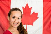 Beautiful asian woman, a sports fan, standing in front of a Canadian flag