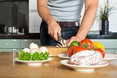 Midsection of young man cutting vegetables on wooden chopping board at kitchen counter