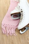 Figure skates with scarf on table close-up