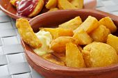 closeup of a plate with typical spanish patatas bravas, fried potatoes with a hot sauce