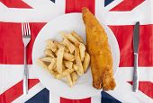 Close-up of junk food with fork and table knife over British flag