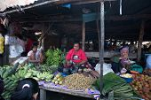 PADANG - AUGUST 25: A vendor sells fresh vegetables and other farm produce at a village market in Pa